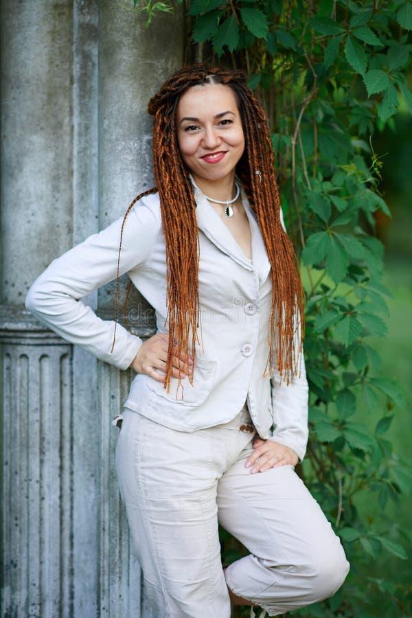 Το μοντέρνο κορίτσι Dreadlocks έντυσε στην άσπρη τοποθέτηση κοντά στις αναδρομικές στήλες στοκ εικόνες με δικαίωμα ελεύθερης χρήσης