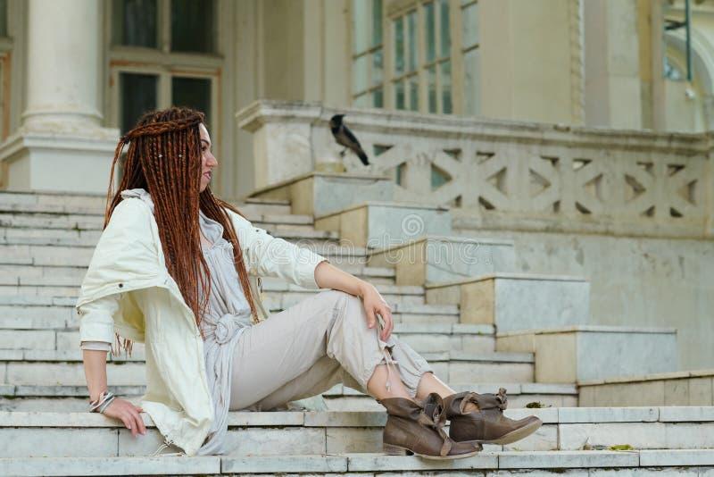 Το μοντέρνο κορίτσι Dreadlocks έντυσε στην άσπρη τοποθέτηση στο παλαιό υπόβαθρο παλατιών στοκ εικόνες με δικαίωμα ελεύθερης χρήσης