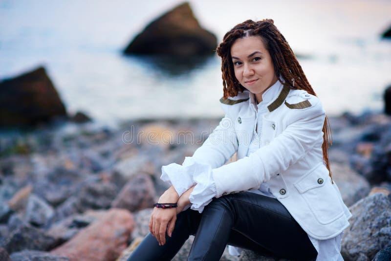 Το μοντέρνο κορίτσι Dreadlocks έντυσε στο άσπρο σακάκι και το μαύρο παντελόνι δέρματος που θέτουν κοντά στη θάλασσα το βράδυ στοκ εικόνες