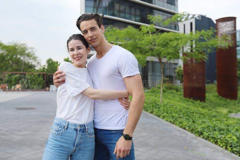 Το μοντέρνο νέο ζεύγος ξοδεύει το χρόνο μαζί υπαίθρια προσελκύει στοκ εικόνα