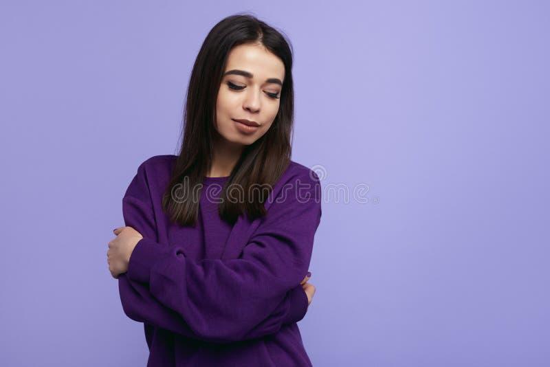 Το μοντέρνο νέο κορίτσι με τις ιδιαίτερες προσοχές, που φορούν το πορφυρό πουλόβερ, που κρατά τα όπλα διέσχισε στεμένος που απομο στοκ φωτογραφία με δικαίωμα ελεύθερης χρήσης