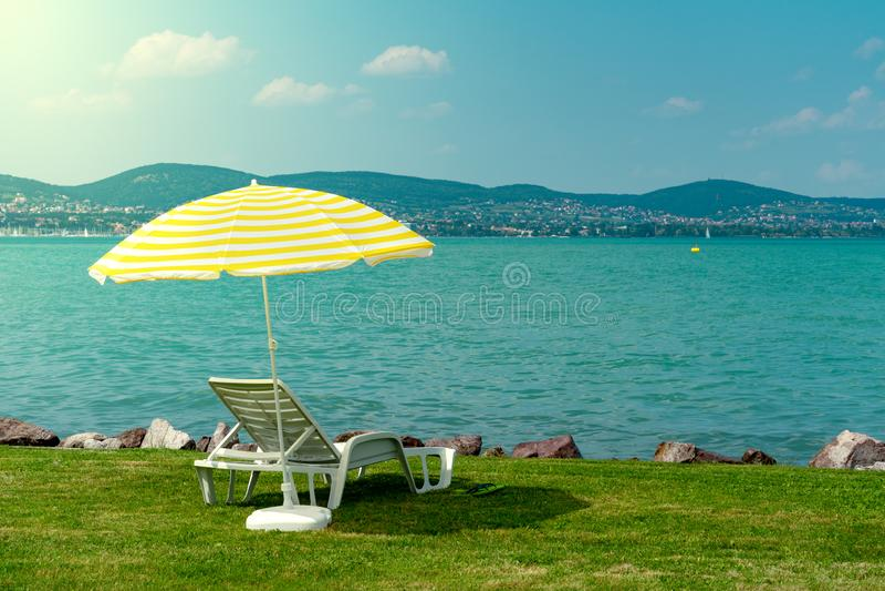 Το μοντέρνο πλαστικό αργοσχόλων με την κίτρινη sunshade λωρίδων ομπρέλα παραλιών στην πράσινη χλόη στην παραλία στο καλοκαίρι κάτ στοκ εικόνα με δικαίωμα ελεύθερης χρήσης