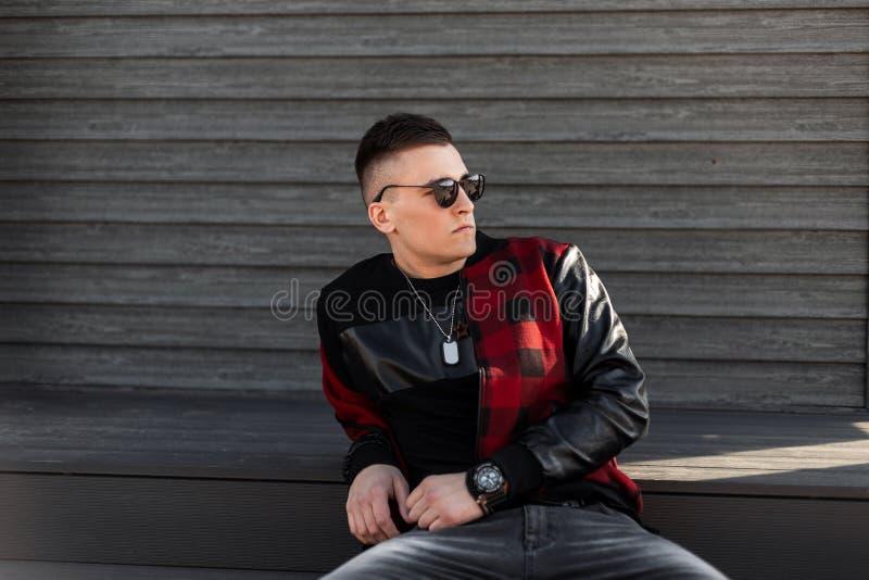 Το μοντέρνο όμορφο άτομο hipster στα μοντέρνα γυαλιά ηλίου που φορούν ένα καπέλο του μπέιζμπολ κάθεται κοντά σε ένα ξύλινο κτήριο στοκ φωτογραφίες