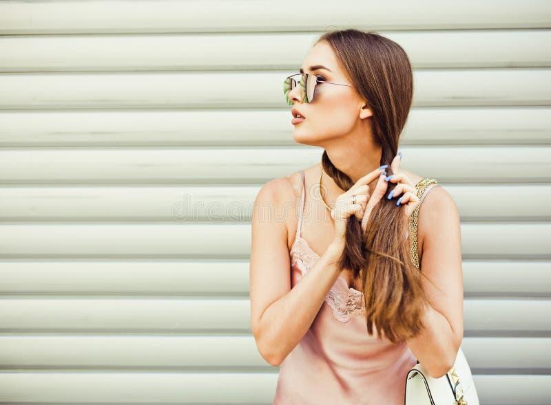 Το μοντέρνο όμορφο κορίτσι brunette στα γυαλιά ηλίου υφαίνει τις πλεξούδες στον τοίχο υποβάθρου Καλοκαίρι στοκ φωτογραφία