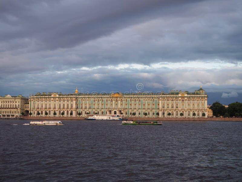 Το Μουσείο Ερμιτάζ στη Αγία Πετρούπολη, με τις τουριστικές βάρκες μπροστά από το, στο υπόβαθρο του δραματικού θυελλώδους ουρανού στοκ φωτογραφία με δικαίωμα ελεύθερης χρήσης