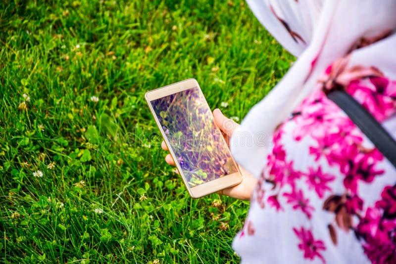 Το μουσουλμανικό κορίτσι που κρατά το κινητό τηλέφωνο στα χέρια της καθμένος στοκ φωτογραφία με δικαίωμα ελεύθερης χρήσης