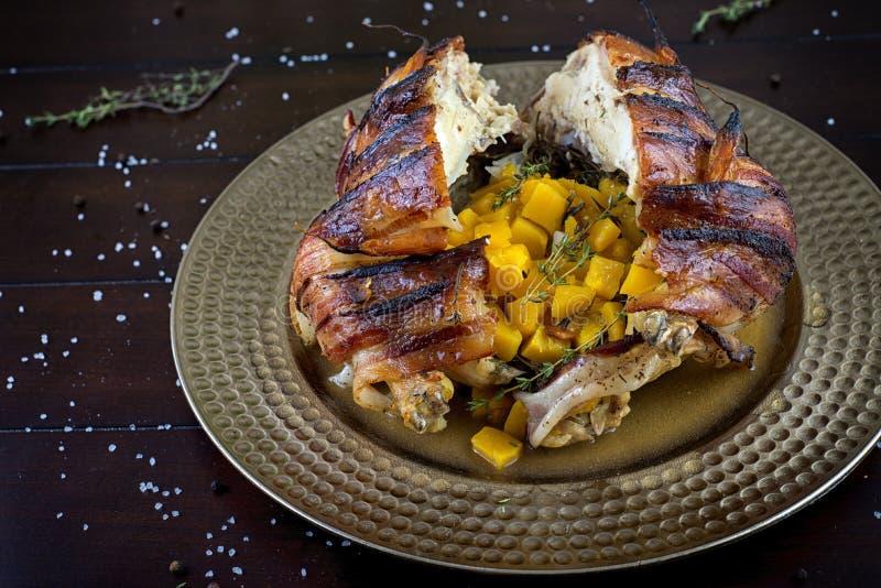 Το μπέϊκον τύλιξε το ψημένο κοτόπουλο που γεμίστηκε με την κολοκύνθη butternut στοκ εικόνες