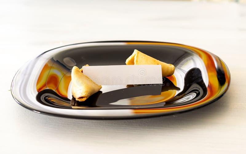 Το μπισκότο τύχης βρίσκεται σε ένα μαύρο πιάτο σε ένα ελαφρύ υπόβαθρο με μια κενή σημείωση στοκ εικόνες με δικαίωμα ελεύθερης χρήσης