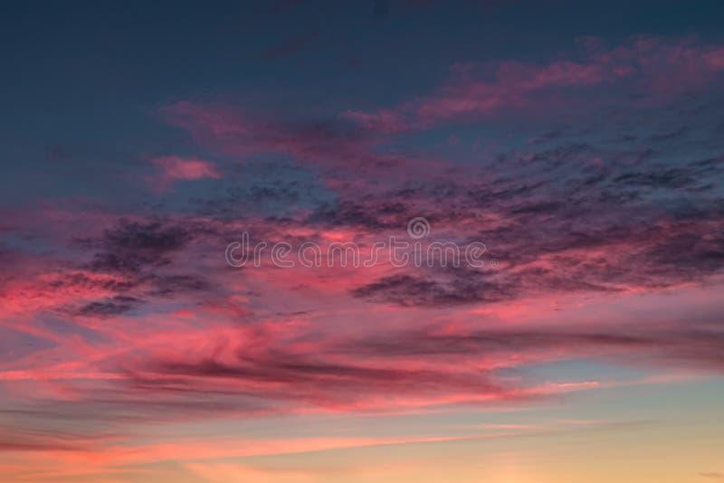 Το μπλε ιώδες κόκκινο υπόβαθρο ουρανού ηλιοβασιλέματος με να εξισώσει το χνουδωτό σγουρό cirrostratus κυλίσματος καλύπτει Καλός θ στοκ φωτογραφία