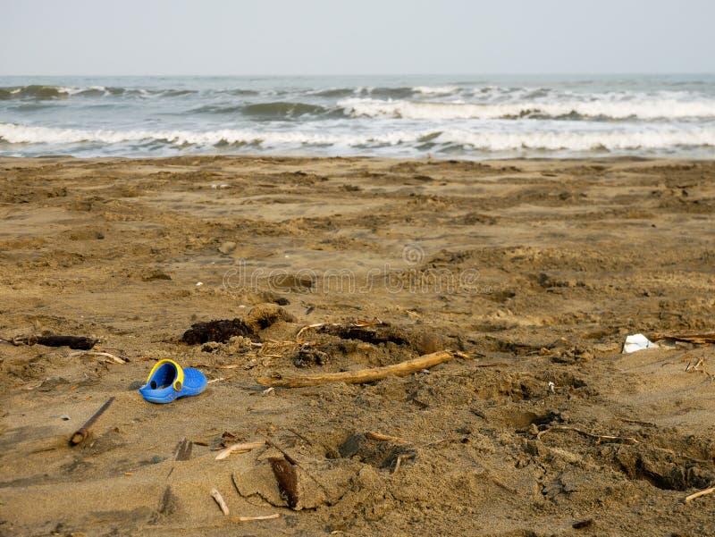 Το μπλε και κίτρινο clog παπούτσι πέταξε σε μια καραϊβική παραλία κοντά στο πλαστικό της Καρχηδόνας Κολομβία στοκ φωτογραφία με δικαίωμα ελεύθερης χρήσης