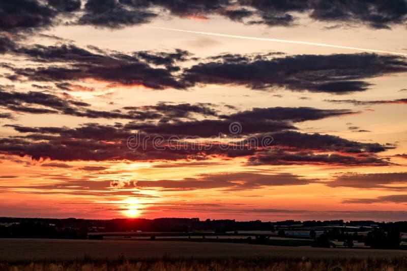 Το μπλε κόκκινο υπόβαθρο ουρανού με να εξισώσει το χνουδωτό σγουρό κύλισμα καλύπτει με τη ρύθμιση του ήλιου Καλός θυελλώδης καιρό στοκ φωτογραφία