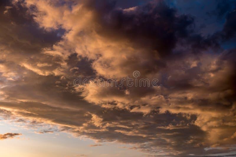 Το μπλε κόκκινο υπόβαθρο ουρανού με να εξισώσει το χνουδωτό σγουρό κύλισμα καλύπτει με τη ρύθμιση του ήλιου Καλός θυελλώδης καιρό στοκ εικόνες