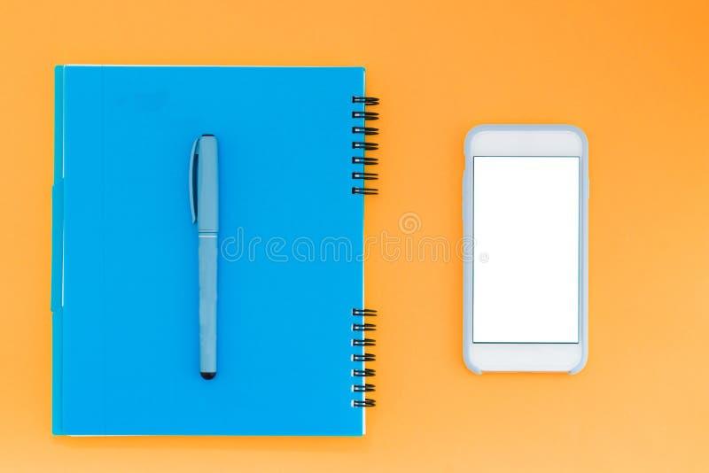Το μπλε μαξιλάρι και η μάνδρα βρίσκονται στο πορτοκαλί υπόβαθρο κοντά snapper Μάνδρα Smartphone και σημειωματάριων Επίπεδος βάλτε στοκ εικόνες
