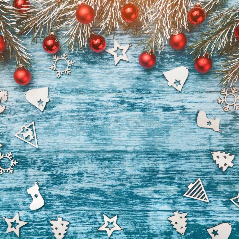 Το μπλε υπόβαθρο Χριστουγέννων με τη διακόσμηση, τα κόκκινα μπιχλιμπίδια, τα ξύλινα διακοσμημένα παιχνίδια και το δέντρο έλατου δ στοκ φωτογραφία με δικαίωμα ελεύθερης χρήσης