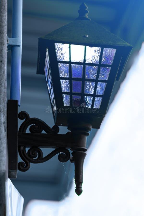 Το μπλε φωτεινό φανάρι κρεμά στην πρόσοψη του κτηρίου οδός, κινηματογράφηση σε πρώτο πλάνο, άσπρο υπόβαθρο r στοκ φωτογραφίες