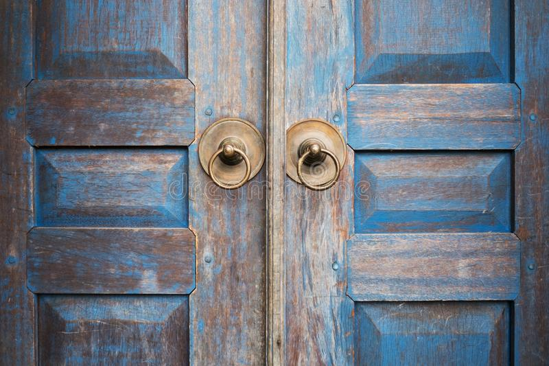 Το μπλε χρωμάτισε την ηλικίας φορεμένη ξύλινη πόρτα με τη λαβή κύκλων μετάλλων στοκ εικόνα
