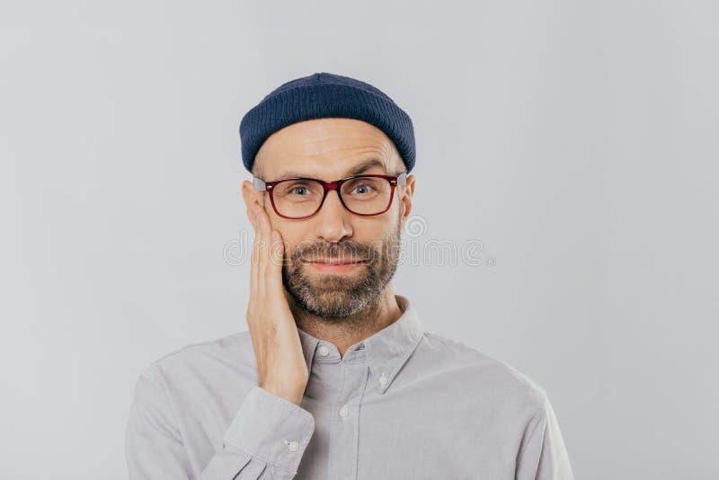 Το μπλε eyed αξύριστο άτομο αυξάνει το φρύδι, κρατά το χέρι στο μάγουλο, κοιτάζει ευτυχώς, φορά eyewear, ντυμένος στο μαύρο καπέλ στοκ εικόνα με δικαίωμα ελεύθερης χρήσης