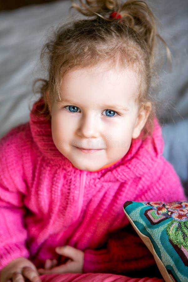 Το μπλε-eyed χαριτωμένο κορίτσι σε ένα ρόδινο σακάκι εξετάζει τη κάμερα στοκ φωτογραφίες με δικαίωμα ελεύθερης χρήσης