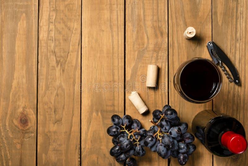 Το μπουκάλι κρασιού κοιλαίνει τις δέσμες των σταφυλιών και του πώματος φελλού στο ξύλινο υπόβαθρο Τοπ άποψη με το διάστημα αντιγρ στοκ φωτογραφία