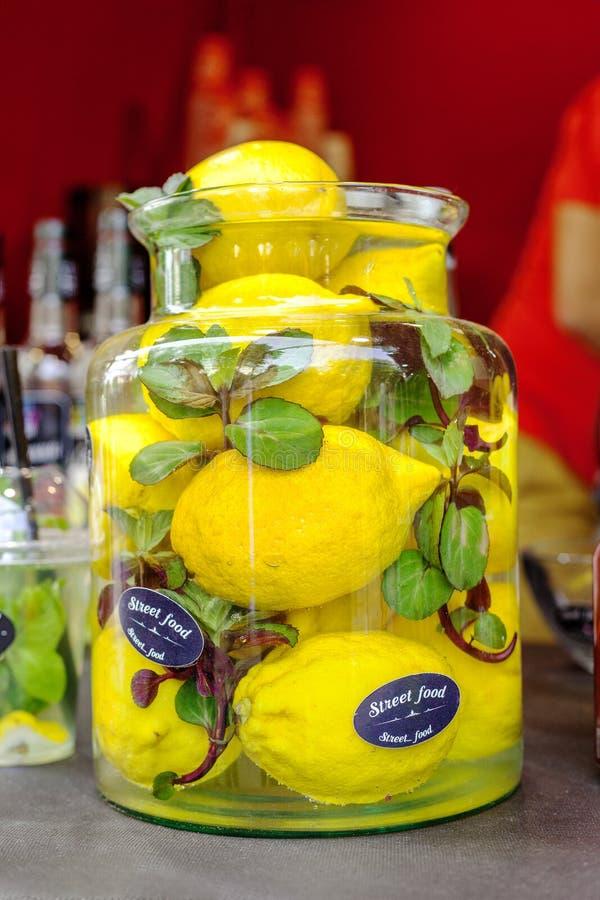 Το μπουκάλι νερό γυαλιού, τα φύλλα μεντών και τα λεμόνια, ημπότισαν το νερό στοκ φωτογραφίες με δικαίωμα ελεύθερης χρήσης