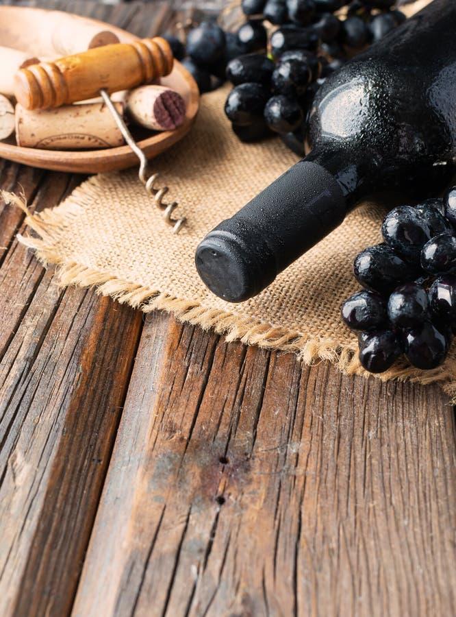 Το μπουκάλι του κόκκινου κρασιού με το φρέσκες σταφύλι και τη δέσμη βουλώνει στον ξύλινο πίνακα στοκ εικόνες