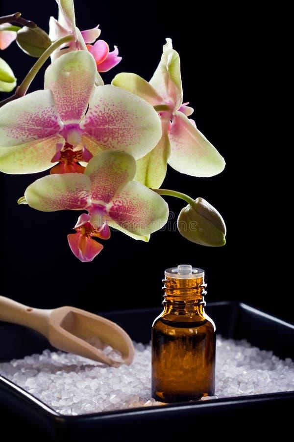 Το μπουκάλι του ουσιαστικού πετρελαίου με orchid ανθίζει στοκ φωτογραφία