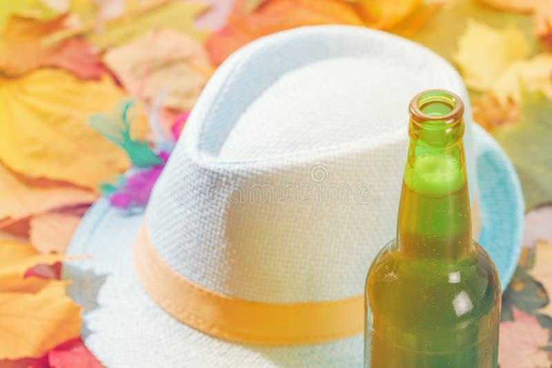 Το μπουκάλι του πιό octoberfest πικ-νίκ πιντών γυαλιού μπύρας στο φυσικό υπόβαθρο με το καπέλο και το φθινόπωρο φεύγει στοκ εικόνα
