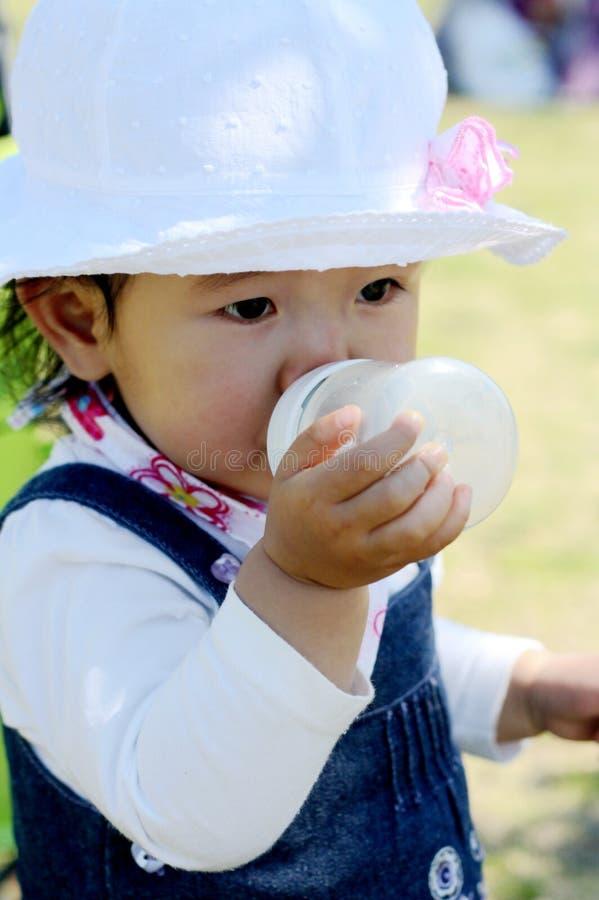 Το μπουκάλι πόσιμου γάλακτος μικρών κοριτσιών στοκ εικόνες