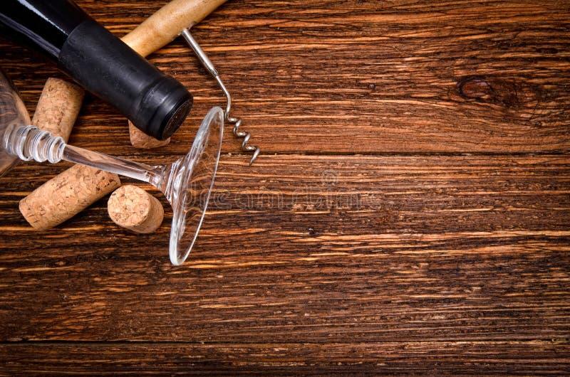 Το μπουκάλι του κρασιού, ανοιχτήρι και βουλώνει στον ξύλινο πίνακα Υπόβαθρο στοκ εικόνες