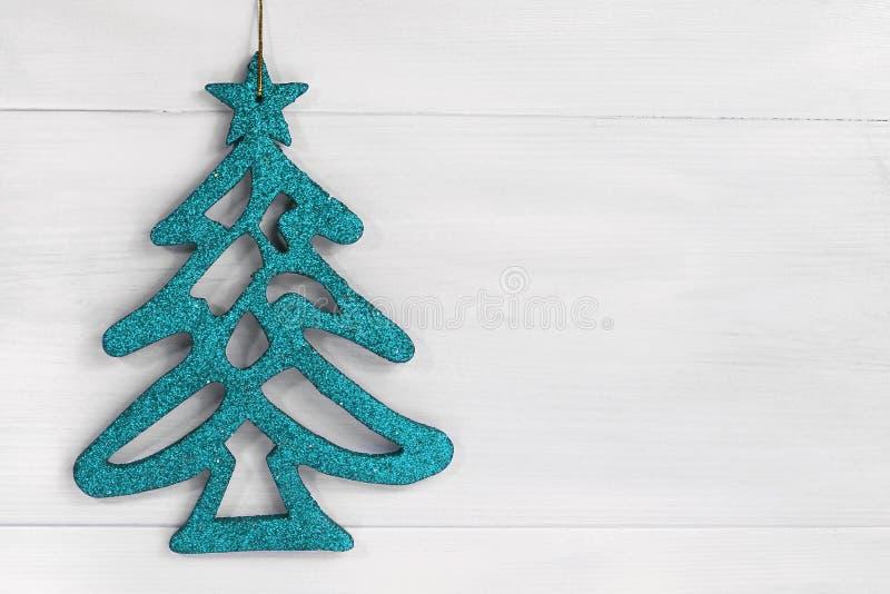 Το μπλε λάμπει χριστουγεννιάτικο δέντρο στο άσπρο ξύλινο υπόβαθρο με το διάστημα αντιγράφων στοκ φωτογραφία με δικαίωμα ελεύθερης χρήσης