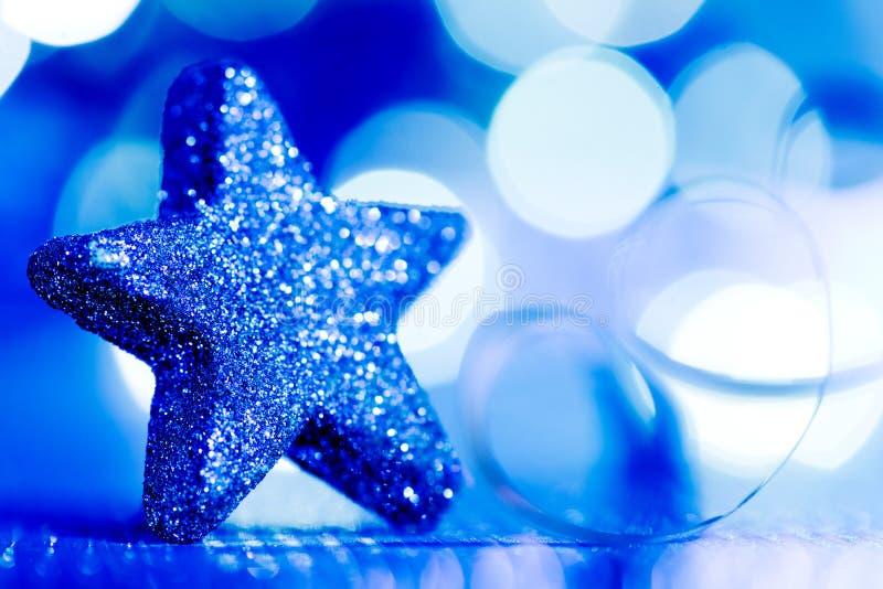 Το μπλε αστέρι Χριστουγέννων και ακτινοβολεί στοκ εικόνες