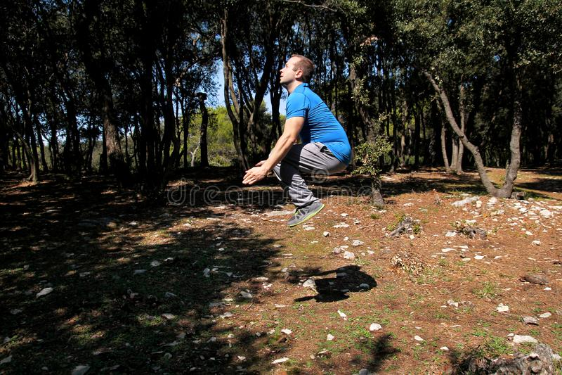Το μυϊκό άτομο που κάνει workout το άλμα επάνω στην άσκηση αέρα στο δασικό όμορφο αθλητικό τύπο που φορά sportswear πηδά επάνω στ στοκ φωτογραφίες με δικαίωμα ελεύθερης χρήσης