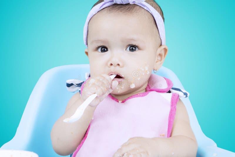 Το μωρό δαγκώνει ένα κουτάλι κουάκερ στοκ εικόνες