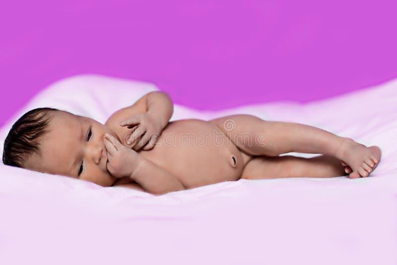 Το μωρό βρίσκεται στο κρεβάτι και απορροφά το δάχτυλό της στοκ εικόνες με δικαίωμα ελεύθερης χρήσης