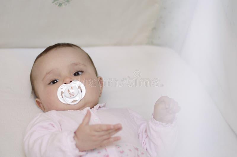 Το μωρό βρίσκεται στο παχνί με τον ειρηνιστή στοκ φωτογραφία