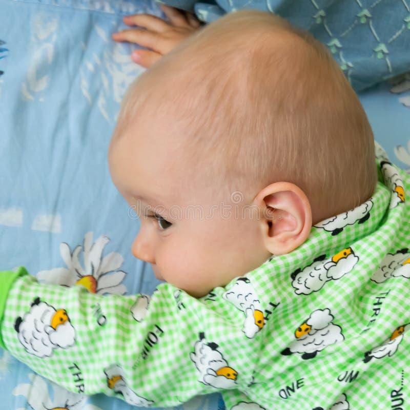 Το μωρό ενός έτους βρεφών σέρνεται σθεναρά στο στόχο του Λίγο εύθυμο αγόρι σε ένα ανοικτό πράσινο κοστούμι με τα πρόβατα στοκ εικόνα