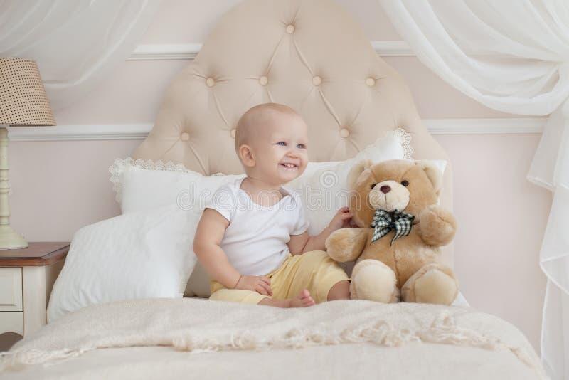 Το μωρό και teddy αφορά το κρεβάτι στην κρεβατοκάμαρα επάνω στο ξύπνημα στοκ εικόνες