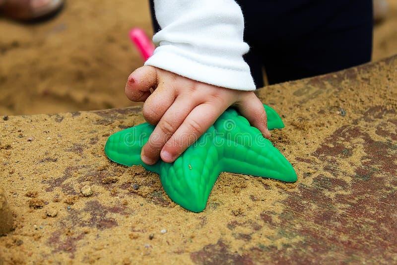 Το μωρό παίζει στο Sandbox με τα πλαστικά εργαλεία παιχνιδιών, αστερίας στοκ εικόνα με δικαίωμα ελεύθερης χρήσης