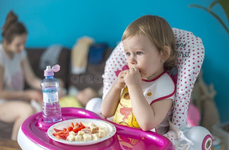 Το μωρό προγευματίζει ντομάτες με το ψωμί στοκ φωτογραφίες