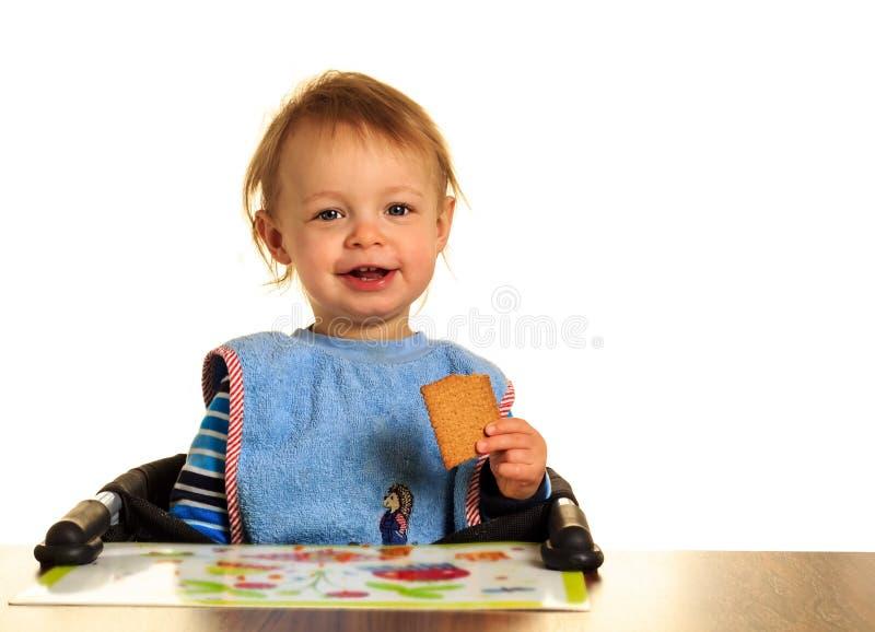 Το μωρό τρώει ένα μπισκότο στοκ φωτογραφία με δικαίωμα ελεύθερης χρήσης