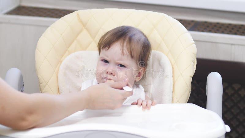 Το μωρό τρώει το κουάκερ από το κουτάλι, φτύνει και χαμογελά τη συνεδρίαση στο highchair στην κουζίνα στοκ φωτογραφία με δικαίωμα ελεύθερης χρήσης