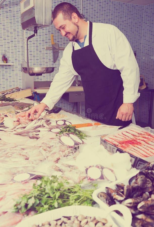 Το μόνιμο συνηθισμένο άτομο παρουσιάζει τα ψάρια αντίθετα στοκ εικόνες