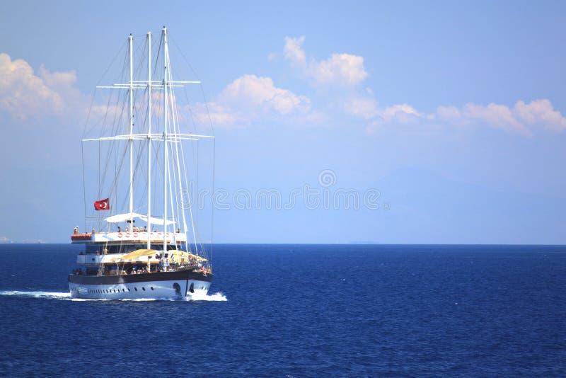 Το μόνο σκάφος, sailboat στη Μεσόγειο με τους τουρίστες εν πλω, άσπρος σωρείτης καλύπτει στο μπλε ουρανό στοκ εικόνα με δικαίωμα ελεύθερης χρήσης
