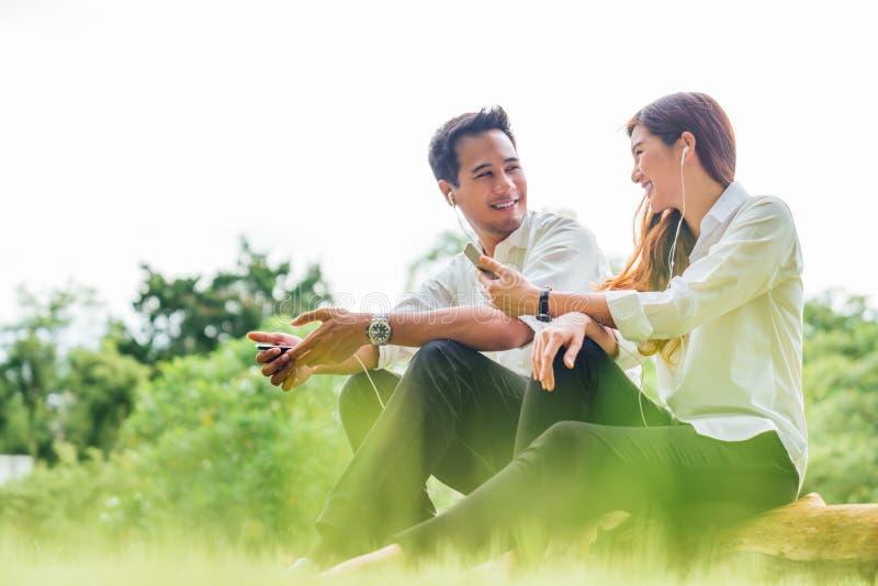Το νέοι ασιατικοί καλοί ζεύγος ή οι φοιτητές πανεπιστημίου κάθεται να ακούσει στη μουσική τραγουδιού στο smartphone μαζί στο πάρκ στοκ εικόνες
