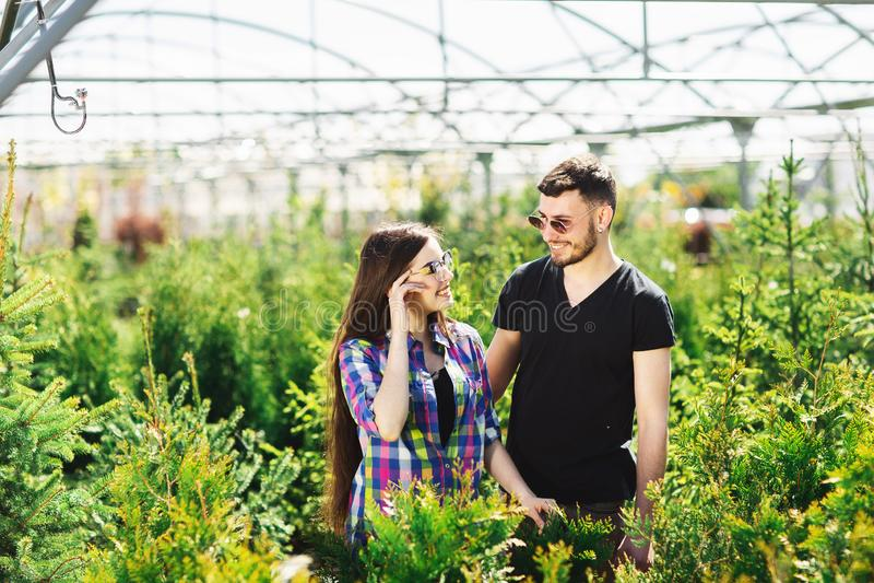Το νέοι ζεύγος, ο άνδρας και η γυναίκα, που στέκονται μαζί στο κέντρο κήπων και επιλέγουν τις εγκαταστάσεις για το πρασίνισμα του στοκ εικόνα με δικαίωμα ελεύθερης χρήσης