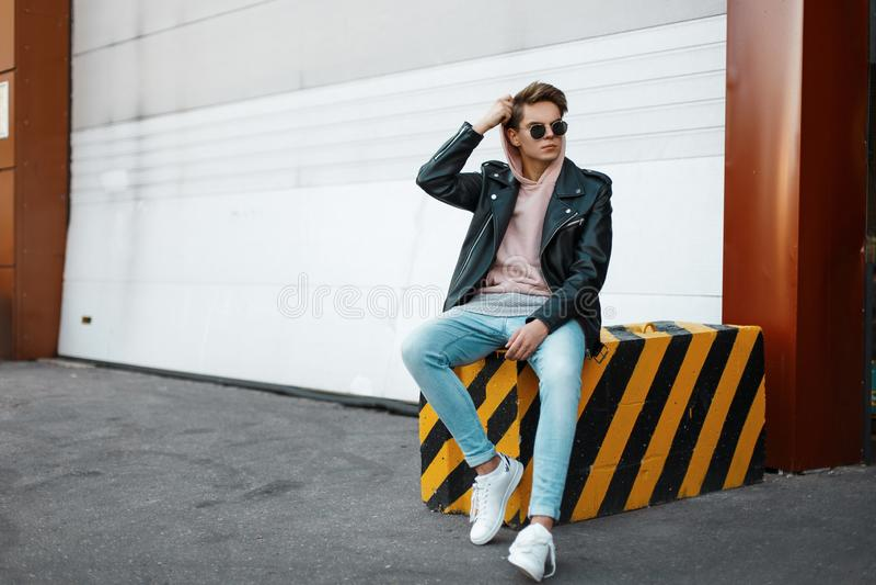 Το νέο άτομο hipster σε μια ρόδινη μπλούζα στα καθιερώνοντα τη μόδα γυαλιά ηλίου σε ένα μαύρο σακάκι στα τζιν στα άσπρα πάνινα πα στοκ εικόνα