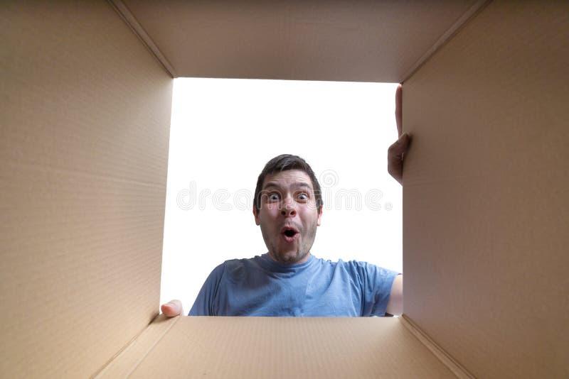 Το νέο έκπληκτο άτομο φαίνεται εσωτερικό κουτί από χαρτόνι στοκ εικόνα