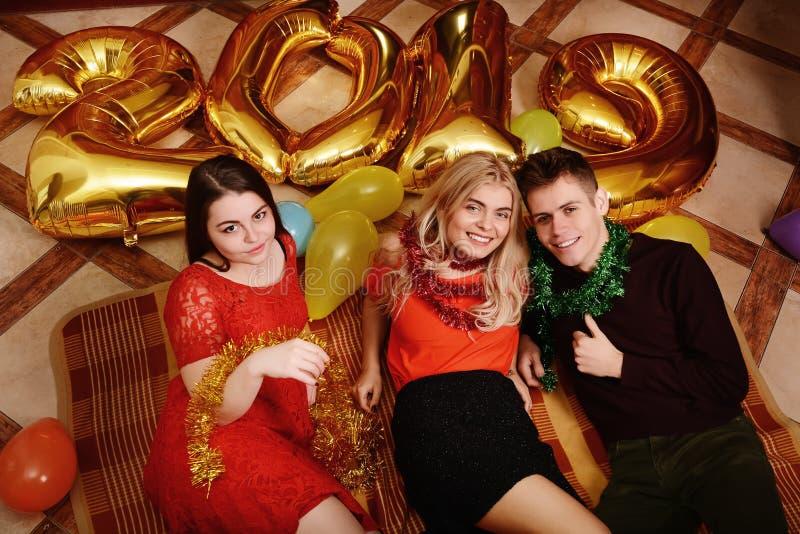 Το νέο έτος του 2019 έρχεται Η ομάδα εύθυμων νέων που φέρνουν τους χρυσούς χρωματισμένους αριθμούς και έχει τη διασκέδαση στο κόμ στοκ εικόνα