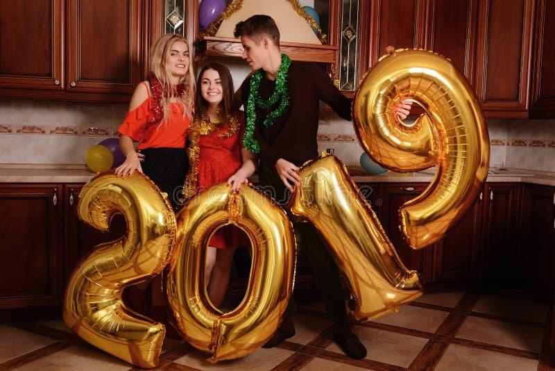 Το νέο έτος του 2019 έρχεται Η ομάδα εύθυμων νέων που φέρνουν τους χρυσούς χρωματισμένους αριθμούς και έχει τη διασκέδαση στο κόμ στοκ εικόνες