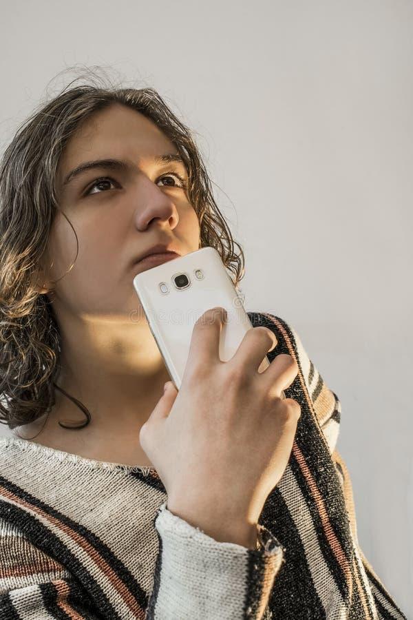 Το νέο αγόρι έντυσε στο πουλόβερ με το κινητό τηλέφωνο στοκ φωτογραφία με δικαίωμα ελεύθερης χρήσης
